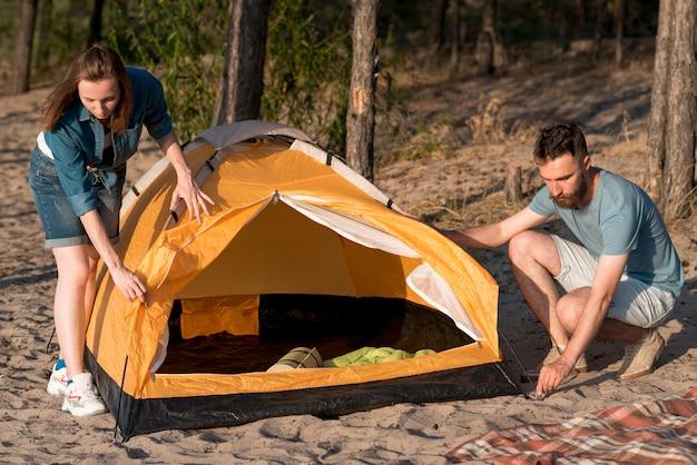 Paare, die ein campingzelt auseinanderbauen