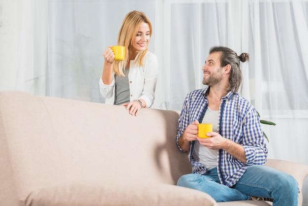 Paare, die ein getränk auf dem sofa teilen