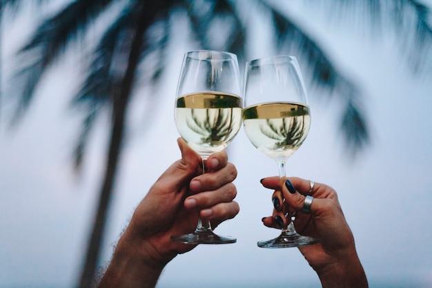 Paare, die ein glas wein am strand genießen