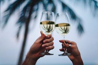 Paare, die ein Glas Wein durch den Strand genießen