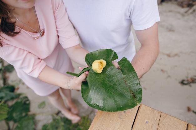 Paare, die ein großes blatt mit einer gelben blume nahaufnahme