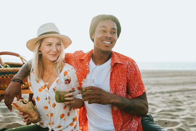 Paare, die ein picknick am strand haben