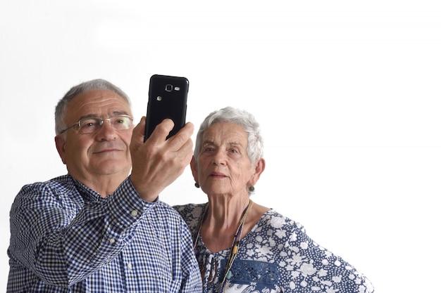Paare, die ein porträt mit dem telefon auf weiß machen