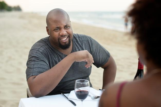 Paare, die ein romantisches abendessen am strand essen