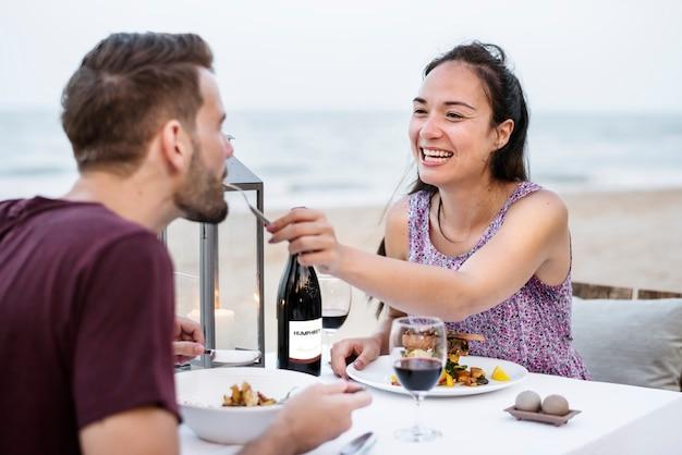 Paare, die ein romantisches abendessen am strand genießen