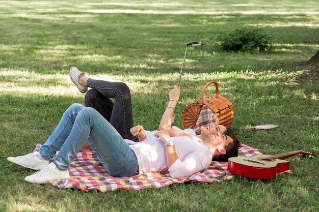 Paare, die ein selfie auf einem picknick nehmen