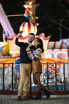Paare, die ein selfie in einem freizeitpark nehmen