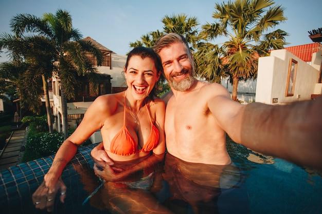 Paare, die ein selfie in einem pool nehmen