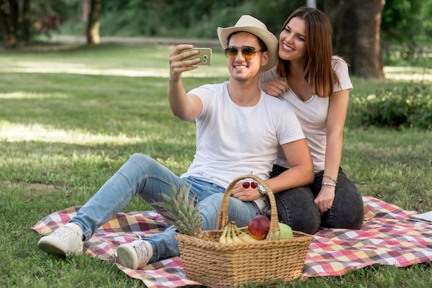Paare, die ein selfie nehmen und am picknick lächeln