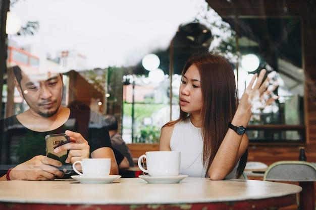 Paare, die ein telefon an einem café verwenden