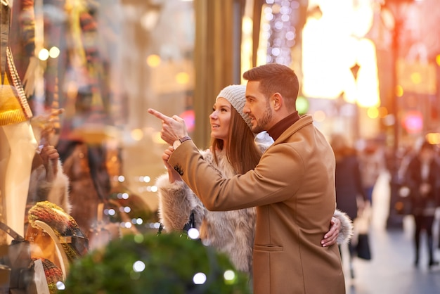 Paare, die ein weihnachtsschaufenster überprüfen