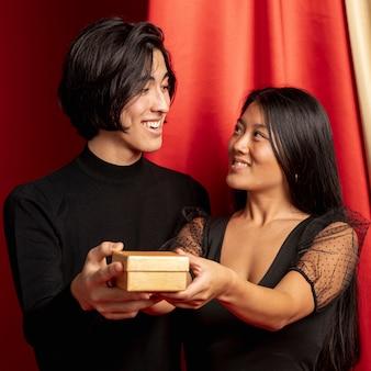 Paare, die einander halten geschenk nach chinesischem neuem jahr betrachten
