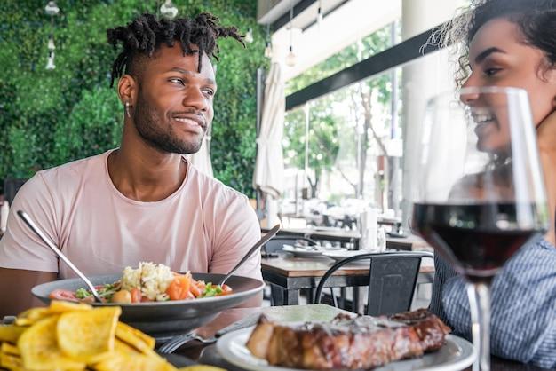 Paare, die eine gute zeit zusammen genießen und verbringen, während sie ein date in einem restaurant haben.