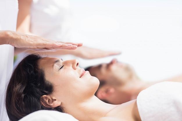 Paare, die eine kopfmassage vom masseur in einem badekurort empfangen