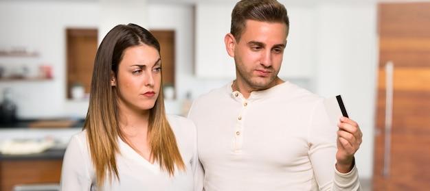 Paare, die eine kreditkarte ohne geld in einem haus nehmen
