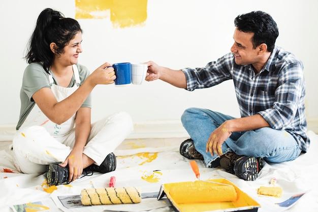 Paare, die eine pause vom malen der wände machen