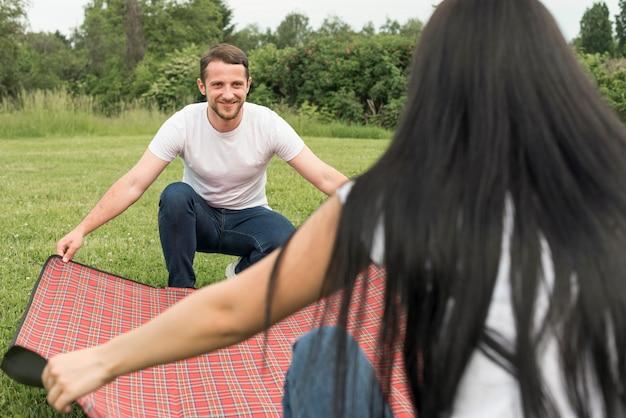Paare, die eine picknickdecke legen