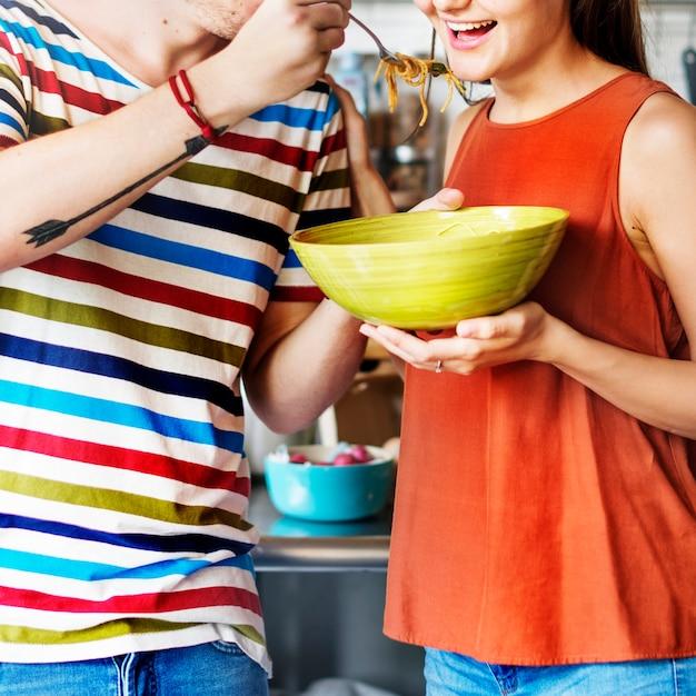 Paare, die eine schüssel spaghettis essend teilen