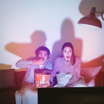 Paare, die einen horrorfilm aufpassen