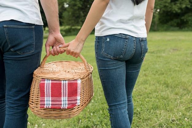 Paare, die einen picknickkorb halten