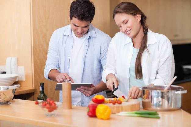 Paare, die einen tablet-computer verwenden, um zu kochen