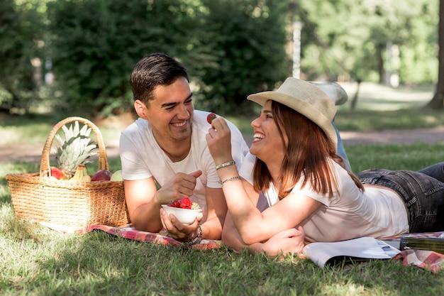 Paare, die erdbeeren am picknick essen
