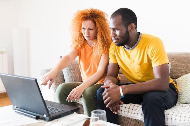 Paare, die etwas auf einem laptop überprüfen