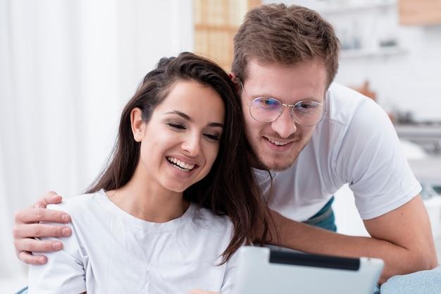 Paare, die etwas auf einer tablette aufpassen