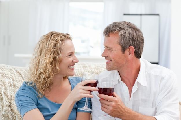 Paare, die etwas rotwein im wohnzimmer trinken