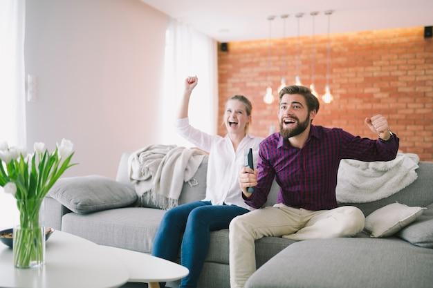 Paare, die fernsehen auf couch genießen