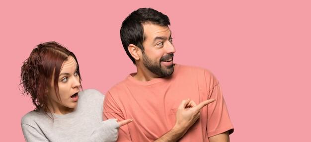 Paare, die finger zur seite mit einem überraschten gesicht zeigen