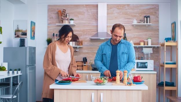 Paare, die frisches gemüse für gesunden salat in der küche mit scharfen messern schneiden. kochen, das gesundes bio-lebensmittel glücklich zusammen lebensstil zubereitet. fröhliches essen in der familie mit gemüse