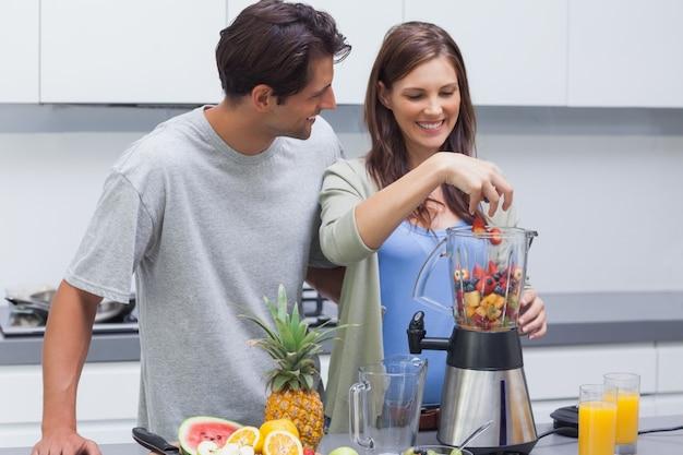 Paare, die früchte in mischmaschine setzen
