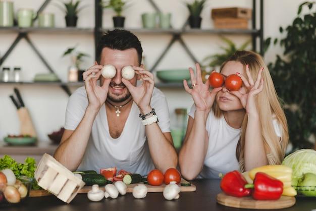 Paare, die ganzes gemüse über augen in der küche halten