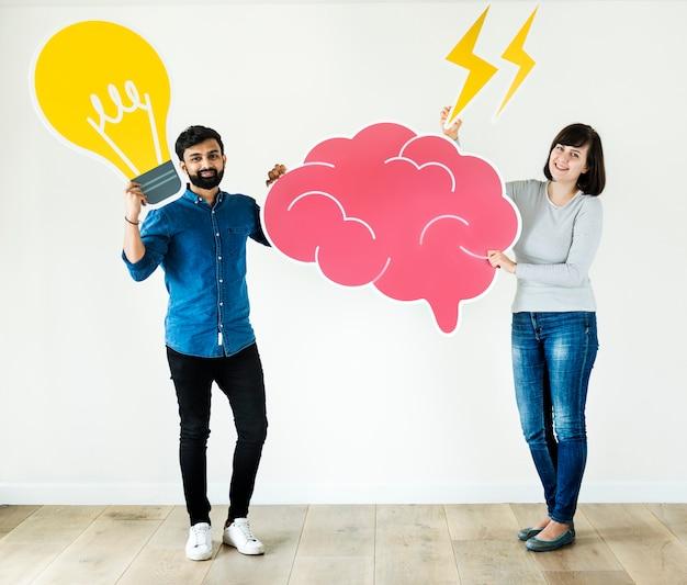 Paare, die gehirn- und glühlampeikoneninnovation und ideenkonzept halten