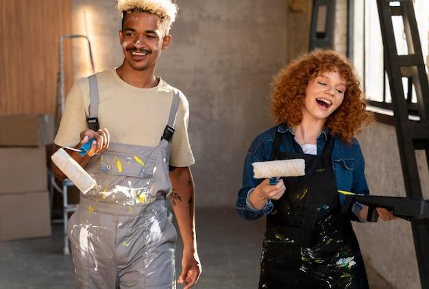 Paare, die gemeinsam die wände ihres neuen zuhauses streichen