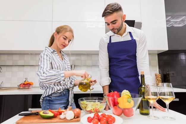 Paare, die gemüsesalat mit olivenöl kochen