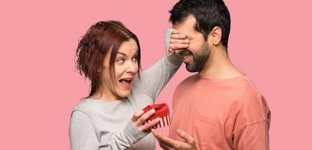 Paare, die geschenkbox über lokalisiertem rosa hintergrund halten