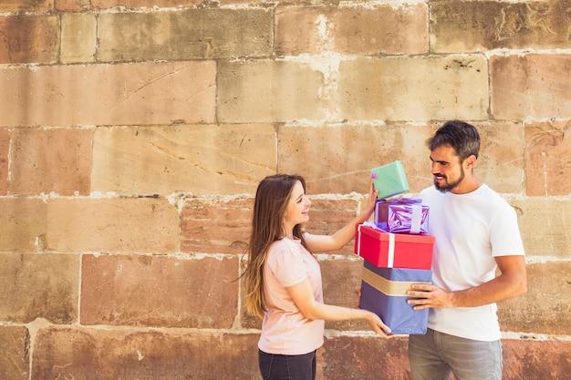 Paare, die geschenke vor wand stapeln