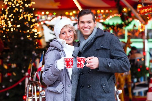 Paare, die gewürzten wein auf weihnachtsmarkt trinken