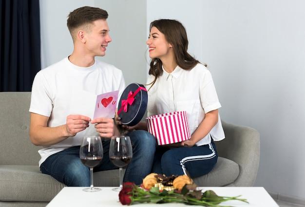 Paare, die große runde geschenkbox auf couch öffnen