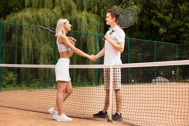 Paare, die hände auf tennisplatz rütteln