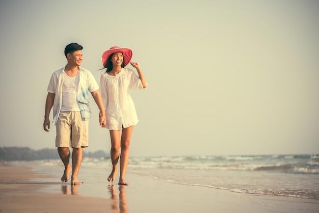 Paare, die hände halten strand tummeln glücklich