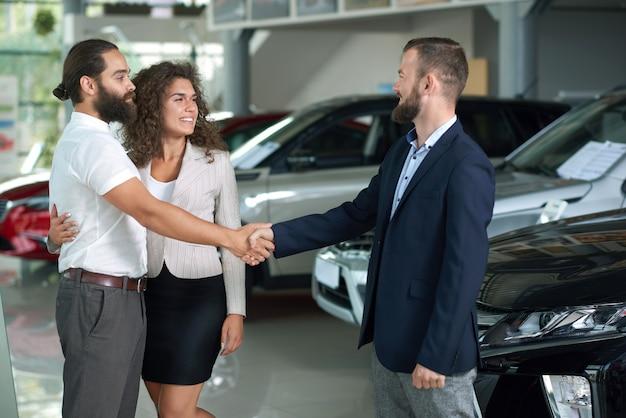 Paare, die hände mit dem autohändler, kaufendes automobil rütteln.