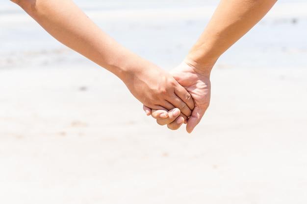 Paare, die ihre hände am strand zusammenhalten