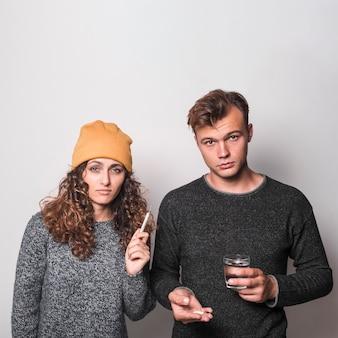 Paare, die ihre nase mit seidenpapier auf grauem hintergrund durchbrennen