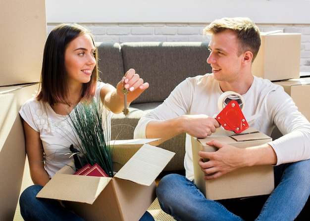 Paare, die ihre sachen in kästen verpacken