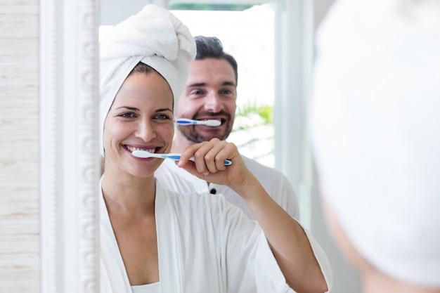 Paare, die ihre zähne im badezimmer putzen