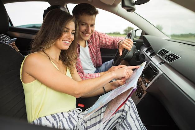 Paare, die im auto zeigt auf karte sitzen