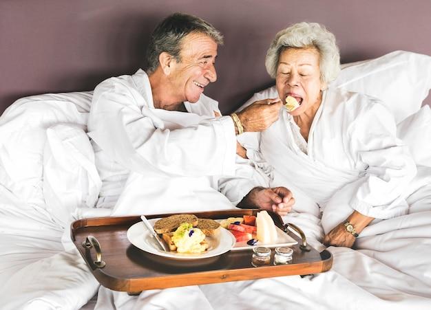 Paare, die im bett frühstücken